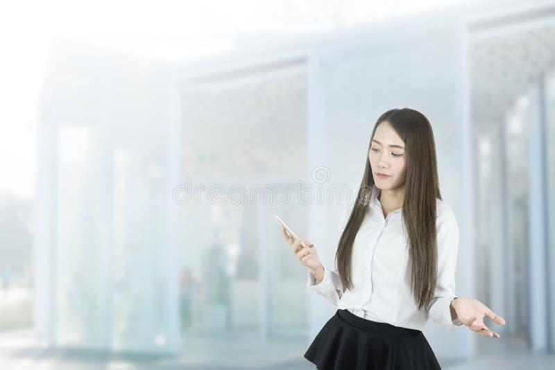 Donna di affari asiatica confusa che per mezzo dello smartphone immagine stock libera da diritti
