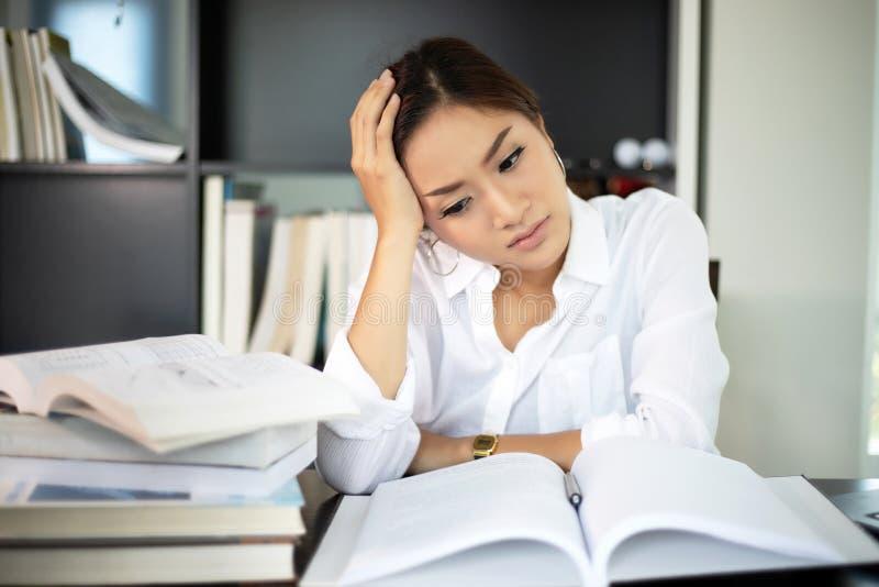 Donna di affari asiatica e studentessa seria circa la lettura immagine stock