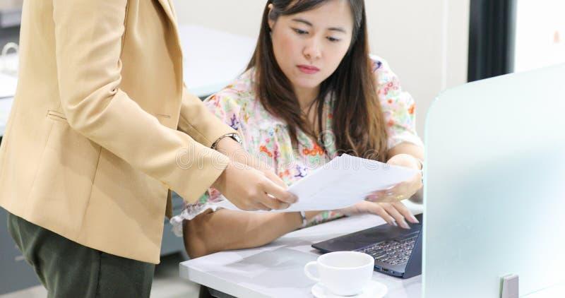 Donna di affari asiatica seria circa il lavoro e che per mezzo del taccuino per i soci commerciali che discutono i documenti e le fotografia stock