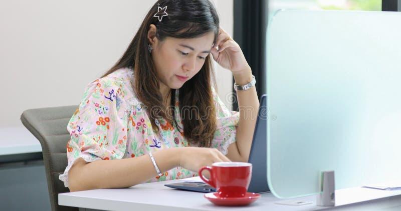 Donna di affari asiatica seria circa il lavoro e che per mezzo del taccuino per i soci commerciali che discutono i documenti e le fotografia stock libera da diritti