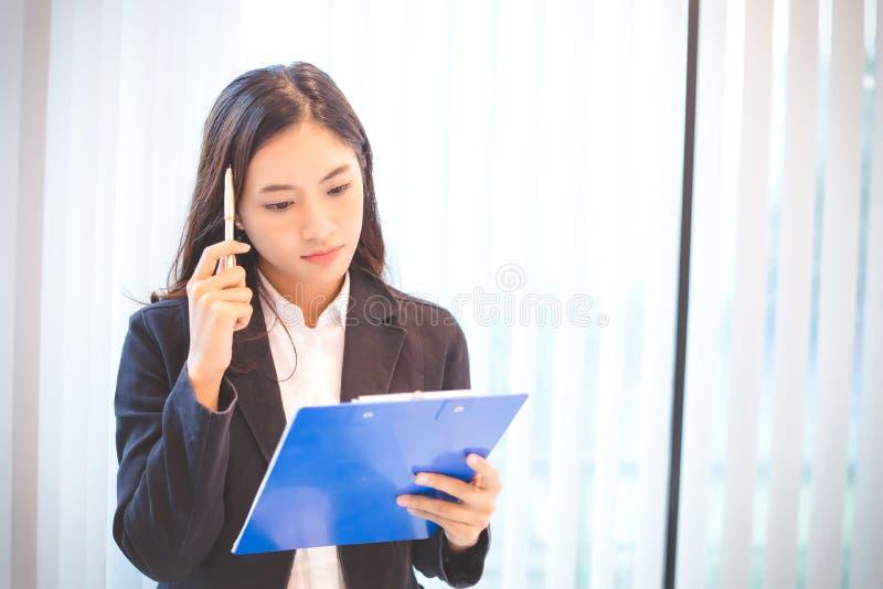 Donna di affari asiatica seria circa il lavoro fatto fino al headac immagine stock libera da diritti