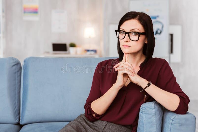 Donna di affari astuta che tocca il suoi mento e pensiero immagini stock