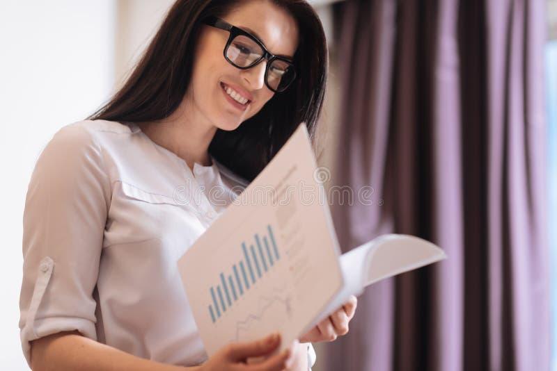 Donna di affari astuta piacevole che lavora con i documenti immagini stock