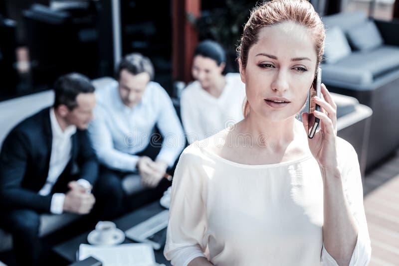 Donna di affari astuta piacevole che parla sul telefono fotografie stock libere da diritti
