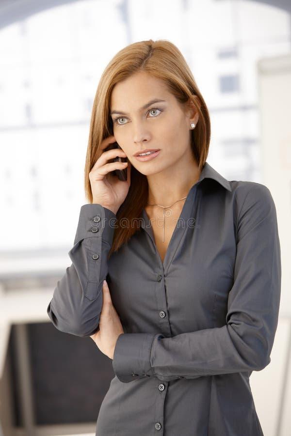 Donna di affari astuta sul telefono fotografia stock