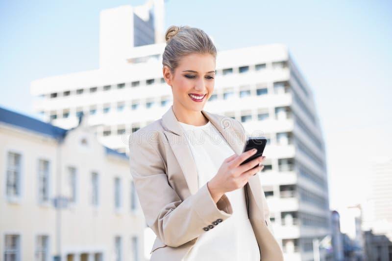 Donna di affari attraente allegra che invia un messaggio di testo fotografie stock