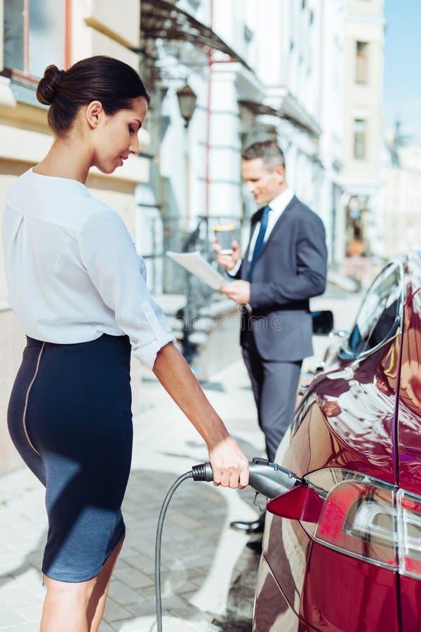 Donna di affari attraente astuta che esamina la sua automobile fotografia stock