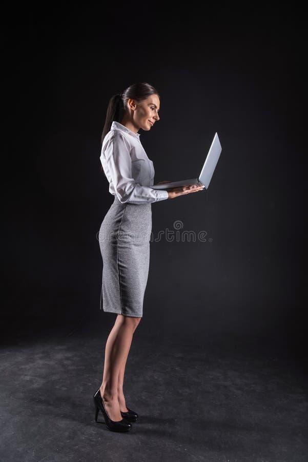 Donna di affari attraente astuta che esamina lo schermo del computer portatile fotografia stock libera da diritti