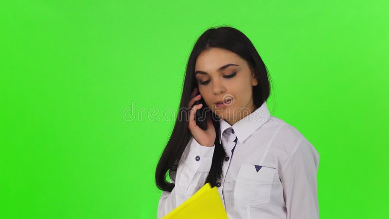 Donna di affari attraente che parla sul telefono, tenente lavagna per appunti fotografia stock libera da diritti