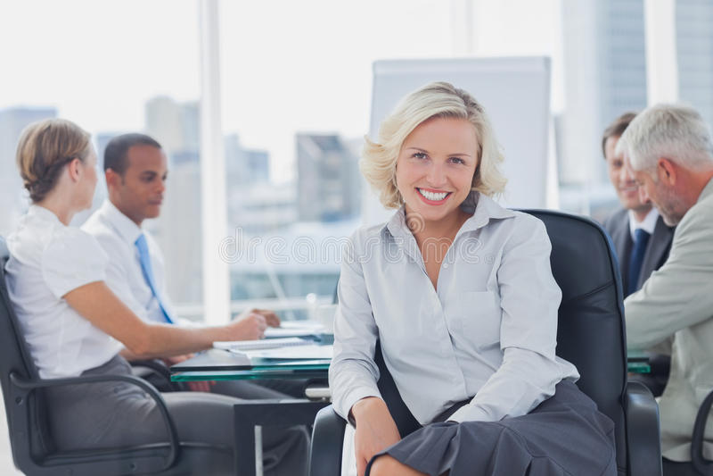 Donna di affari attraente che posa nella sala del consiglio fotografie stock