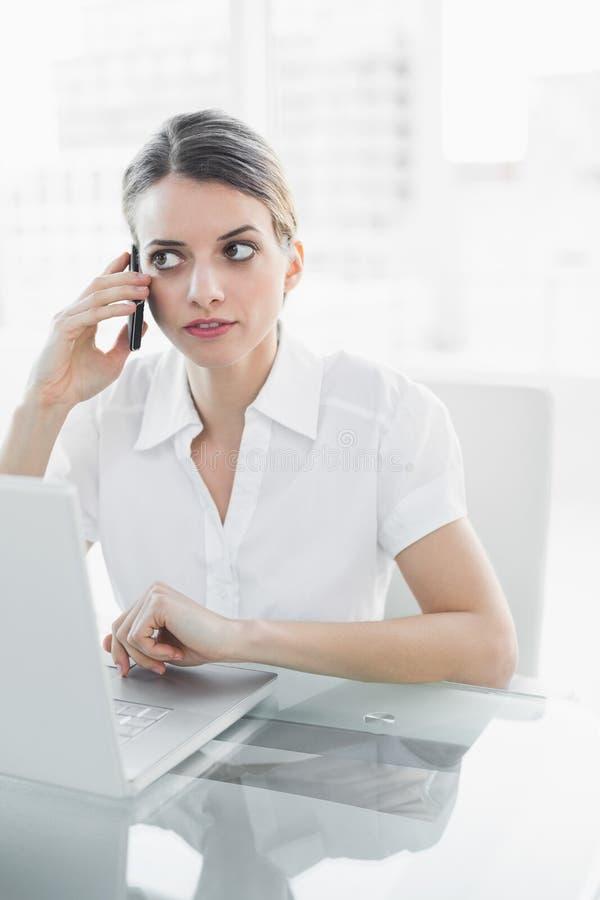Donna di affari attraente che telefona con il suo smartphone immagine stock libera da diritti