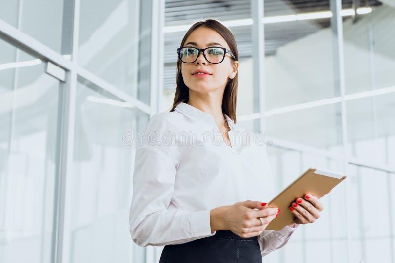 Donna di affari attraente che utilizza una compressa digitale mentre stando in una grande costruzione corporativa fotografia stock libera da diritti