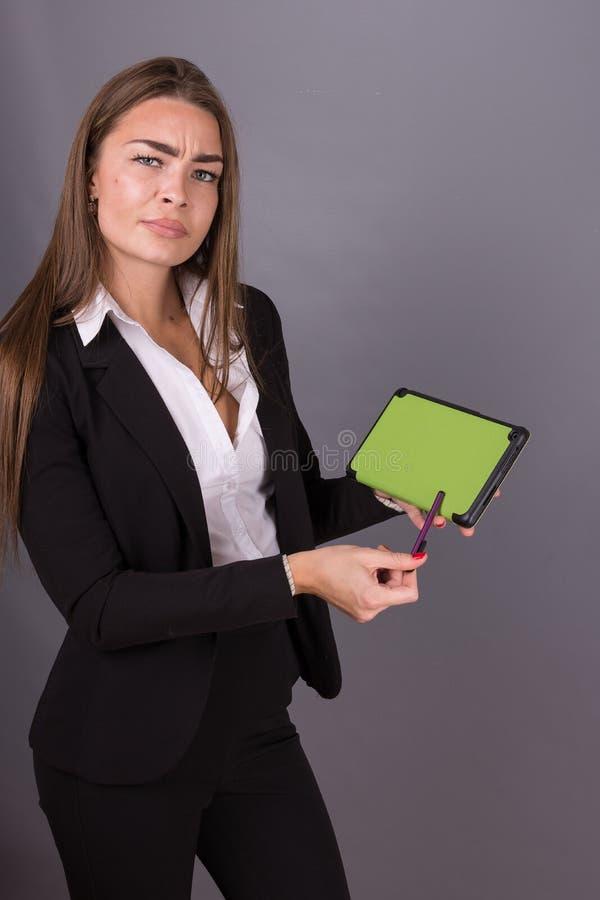 Donna di affari attraente con la compressa che studia le notizie e le idee di presentazione fotografia stock libera da diritti