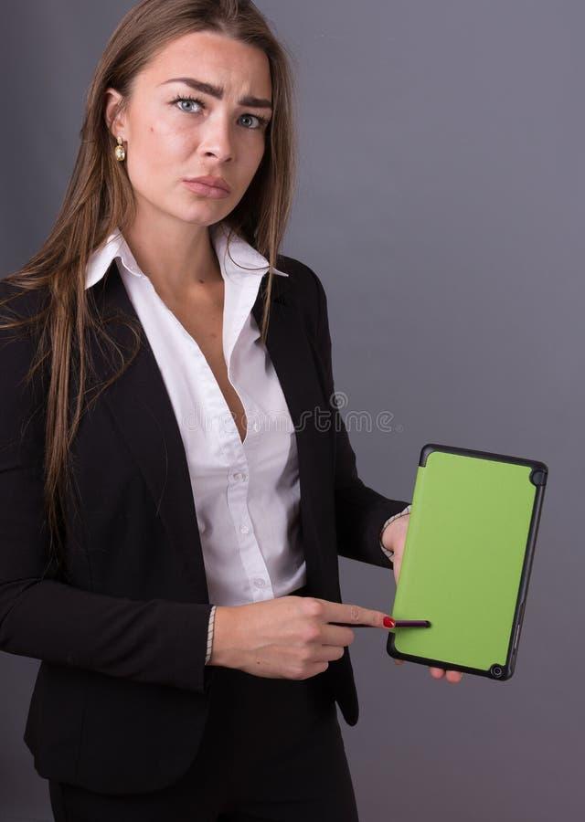 Donna di affari attraente con la compressa che studia le notizie e le idee di presentazione immagine stock