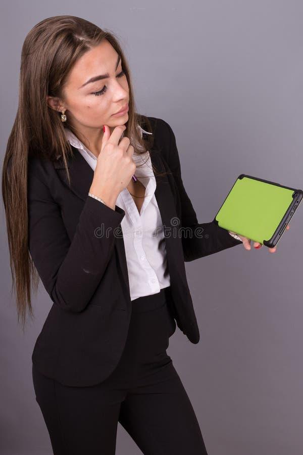 Donna di affari attraente con la compressa che studia le notizie e le idee di presentazione fotografia stock