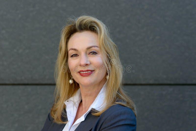 Donna di affari attraente con un sorriso amichevole fotografia stock