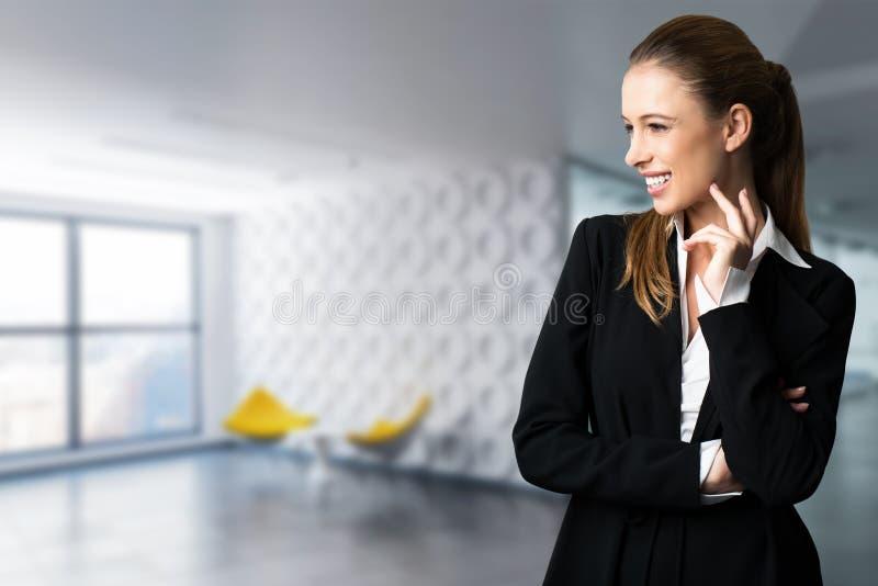 Donna di affari attraente davanti ad una scena dell'ufficio immagine stock