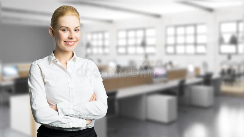 Donna di affari attraente davanti alla scena dell'ufficio fotografia stock libera da diritti