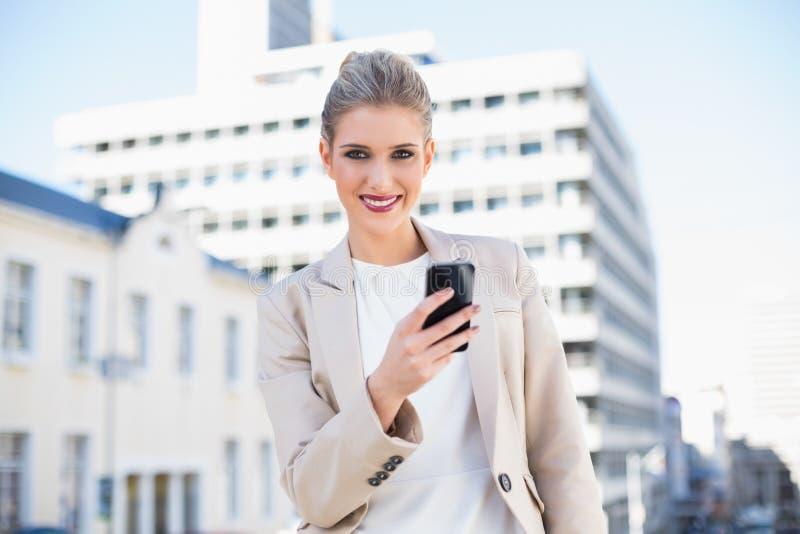Donna di affari attraente felice che invia un messaggio di testo immagine stock libera da diritti