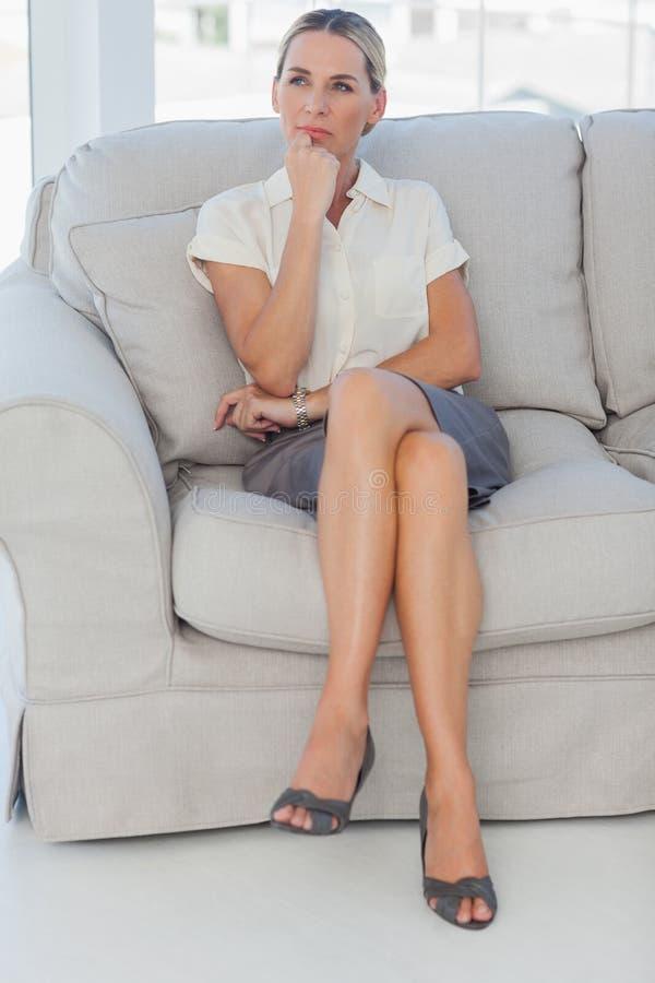 Donna di affari attraente premurosa che posa seduta sul sofà immagine stock