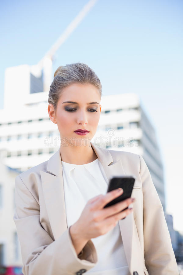 Donna di affari attraente seria che invia un messaggio di testo fotografia stock