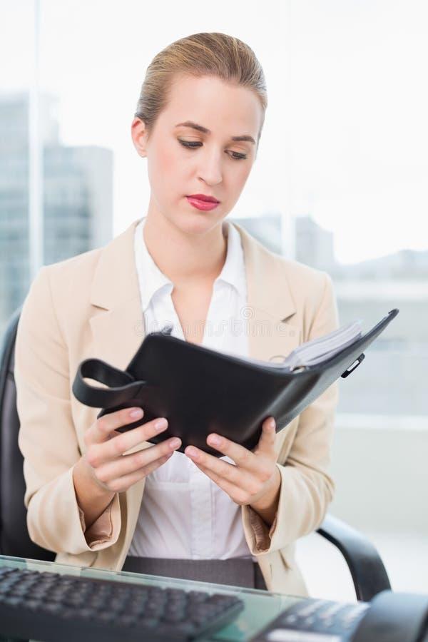 Donna di affari attraente seria che tiene il suo ordine del giorno fotografia stock
