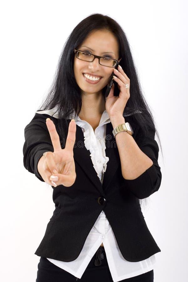 Donna di affari attraente sul segno di vittoria del telefono