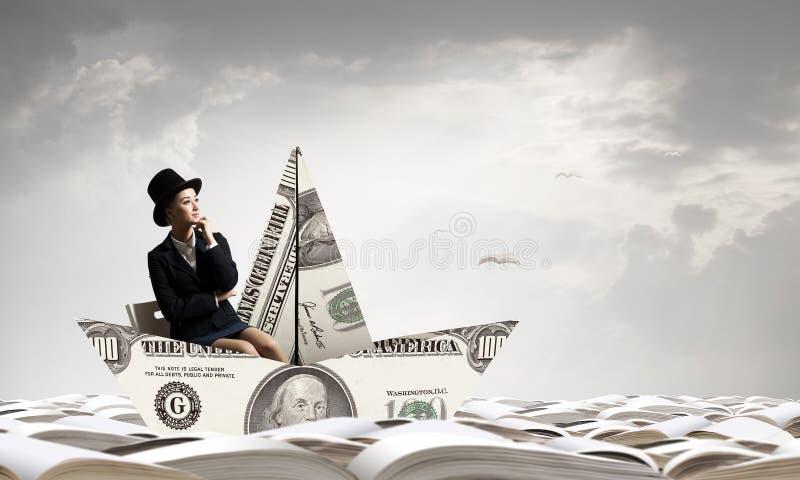 Donna di affari in barca fatta della banconota del dollaro fotografia stock