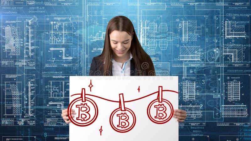 Donna di affari di Bauty che sta nel vestito con il logo di Bitcoin per illustrare l'uso di bitcoin per il commercio o il trasfer immagini stock
