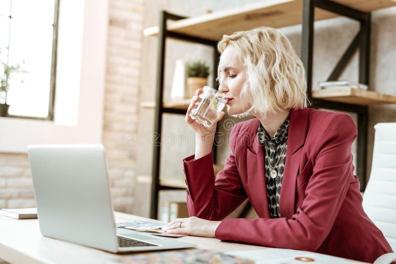 Donna di affari bella dai capelli corti che beve chiara acqua da vetro fotografie stock