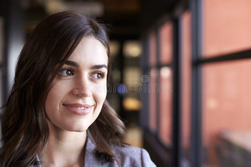 Donna di affari bianca millenaria che guarda dalla finestra in un ufficio, di gran lunga immagine stock