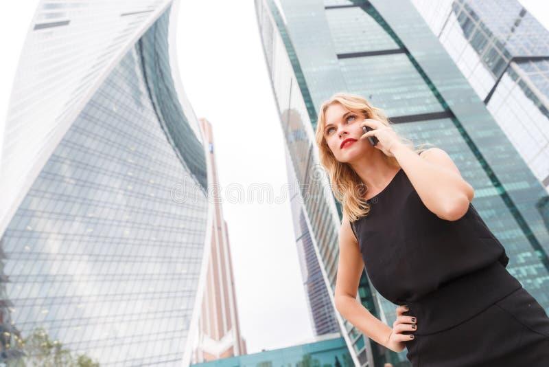 Donna di affari bionda attraente che parla sul telefono fotografia stock