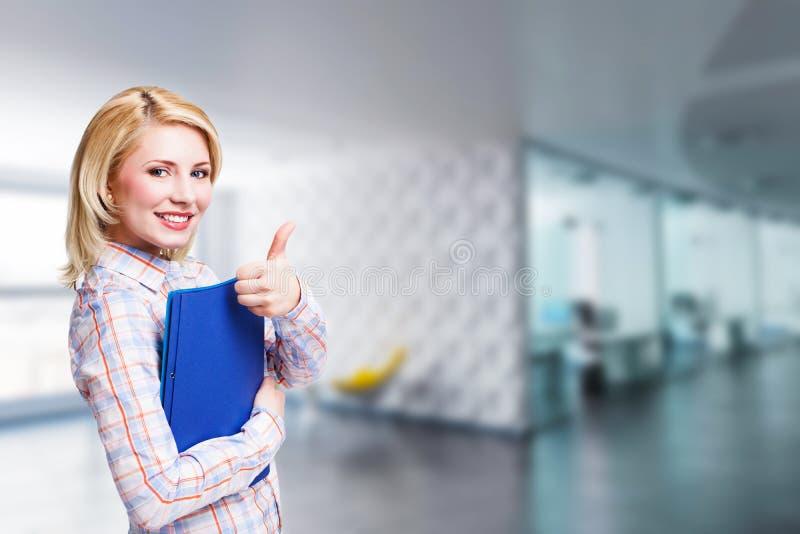 Donna di affari bionda attraente davanti ad una scena dell'ufficio immagine stock