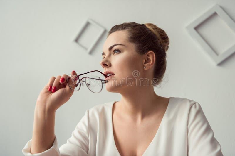 Donna di affari bionda attraente pensierosa con gli occhiali in ufficio moderno immagine stock