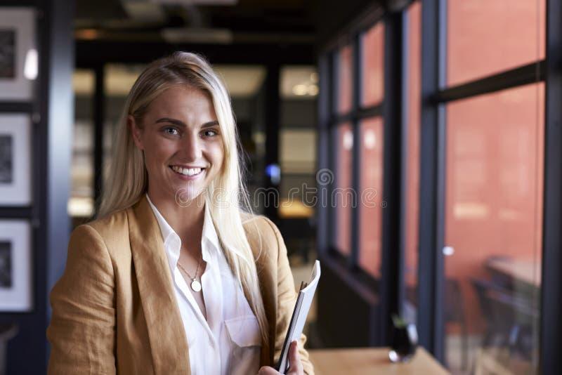 Donna di affari bionda bianca millenaria che sorride alla macchina fotografica dalla finestra in un ufficio, fine su fotografia stock libera da diritti
