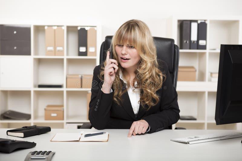 Donna di affari bionda che parla sul telefono fotografia stock