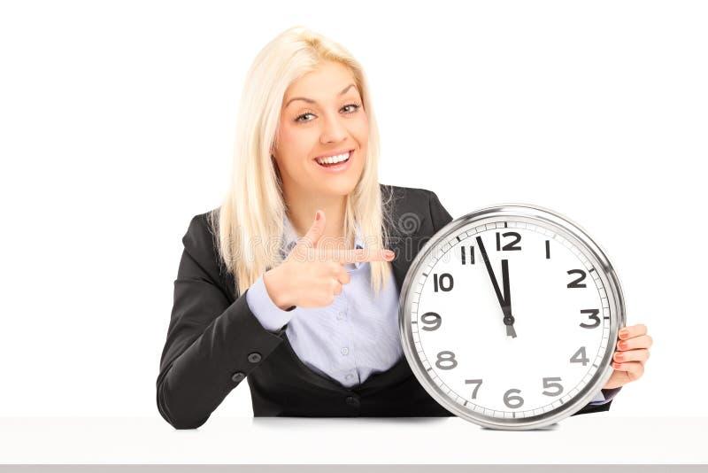 Donna di affari bionda che si siede e che indica su un orologio di parete fotografia stock
