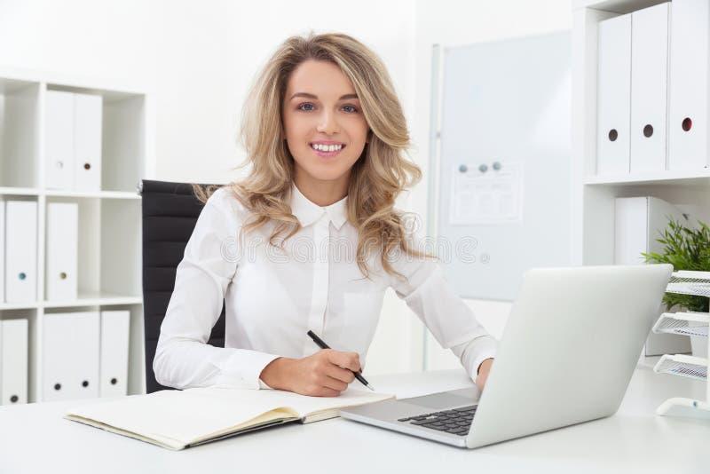 Donna di affari bionda nel suo luogo di lavoro in ufficio immagine stock
