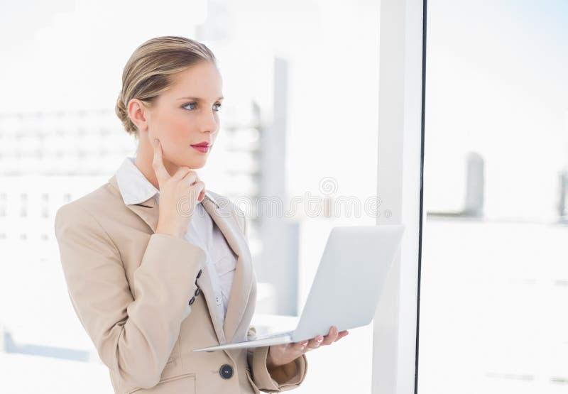 Donna di affari bionda pensierosa che per mezzo del computer portatile fotografia stock