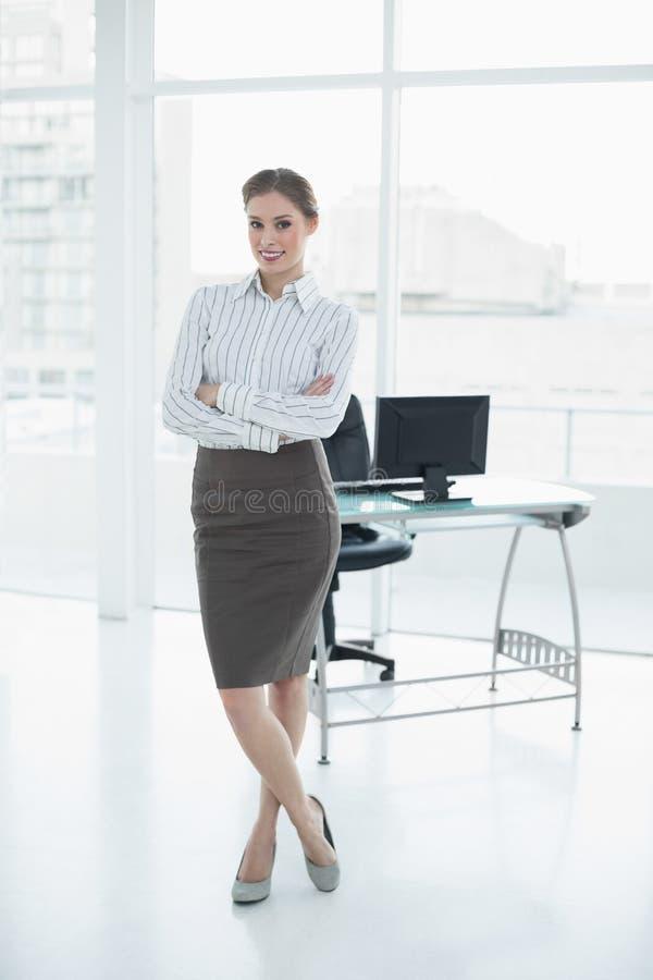 Donna di affari calma adorabile che posa nel suo ufficio con le armi attraversate fotografia stock libera da diritti
