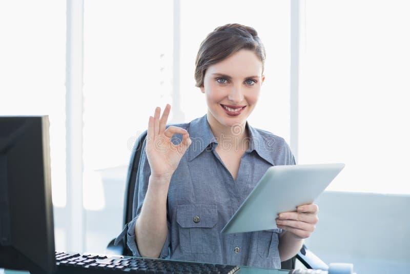 Donna di affari calma attraente che mostra i pollici su mentre tenendo la sua compressa fotografia stock libera da diritti