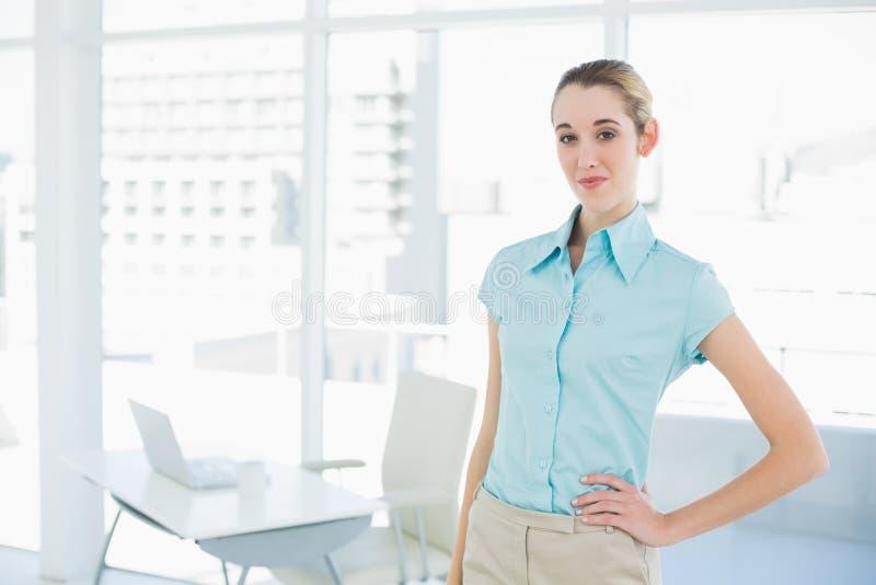 Donna di affari calma attraente che posa nel suo ufficio con la mano sull'anca fotografia stock libera da diritti