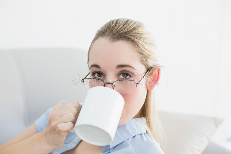 Donna di affari calma attraente che si siede sullo strato che beve dalla tazza immagini stock