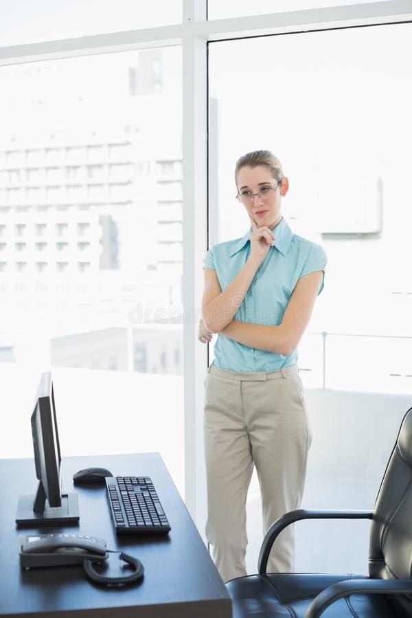 Donna di affari calma che sta premurosa nel suo ufficio fotografia stock libera da diritti