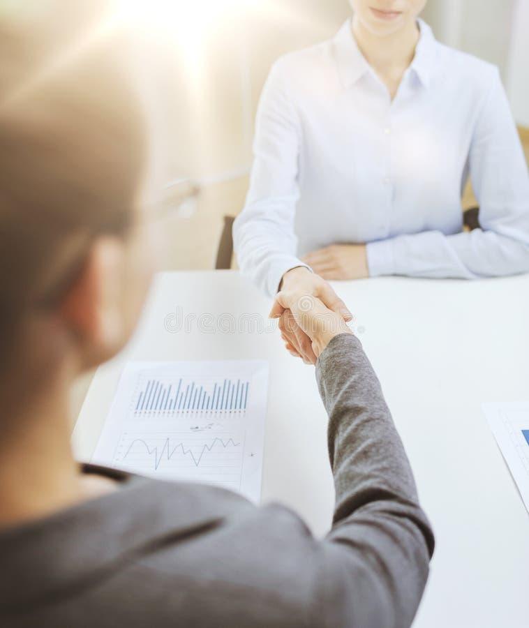 Donna di affari calma due che stringe le mani in ufficio immagine stock libera da diritti