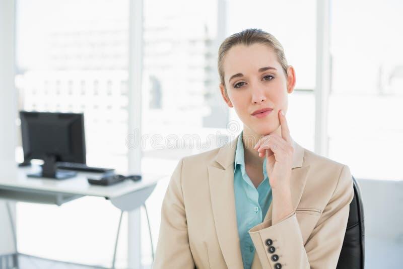 Donna di affari calma premurosa che si siede sulla sua poltrona girevole fotografie stock
