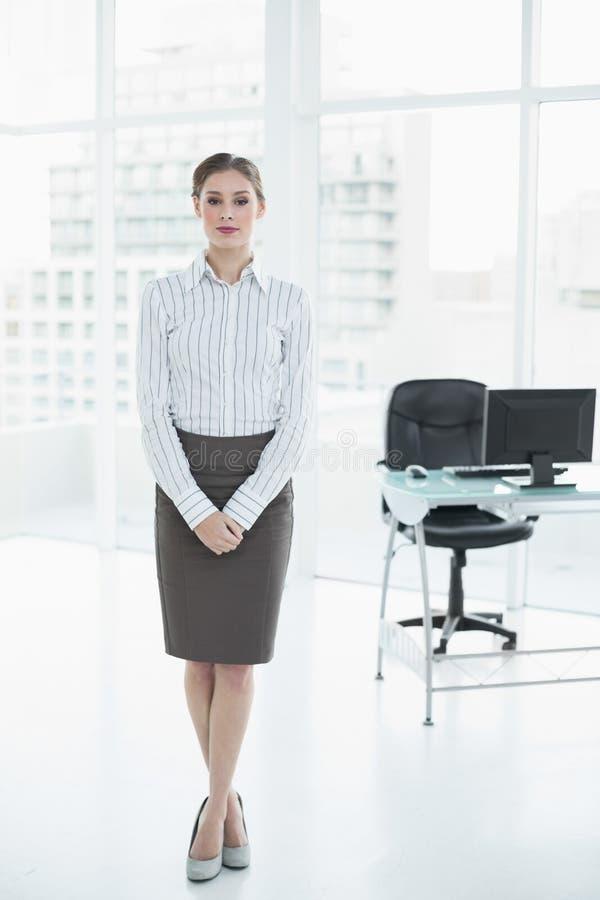 Donna di affari calma seria che posa stare nel suo ufficio fotografia stock