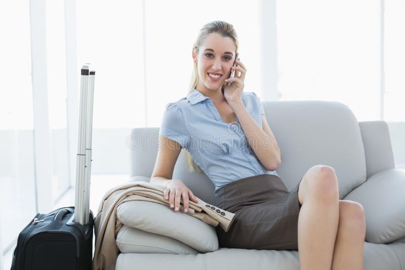 Donna di affari calma splendida che telefona mentre sedendosi sullo strato immagini stock