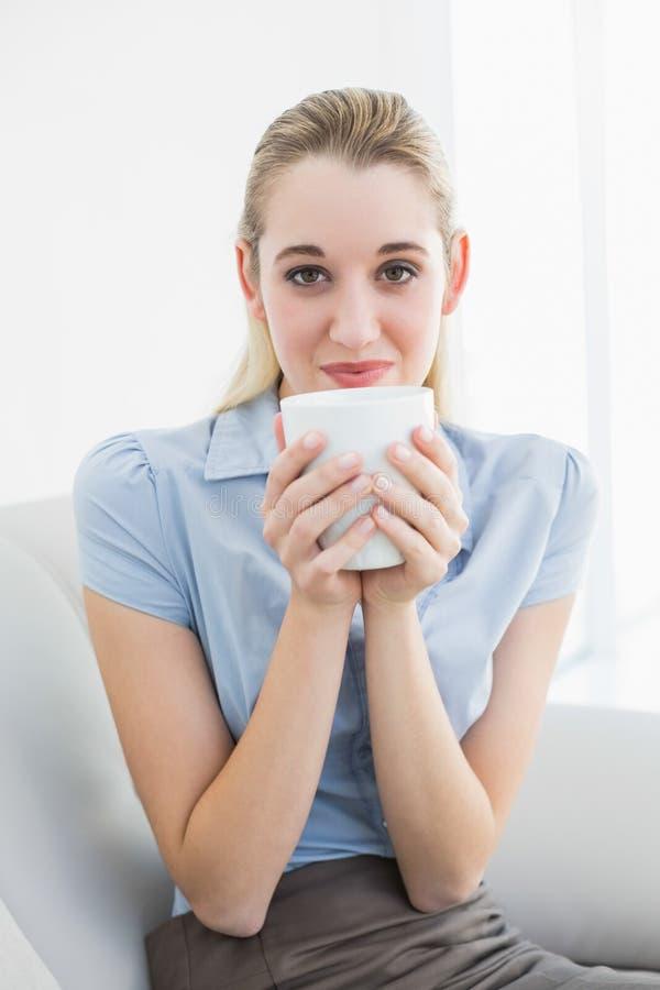 Donna di affari calma splendida che tiene una tazza che odora una tazza fotografie stock libere da diritti