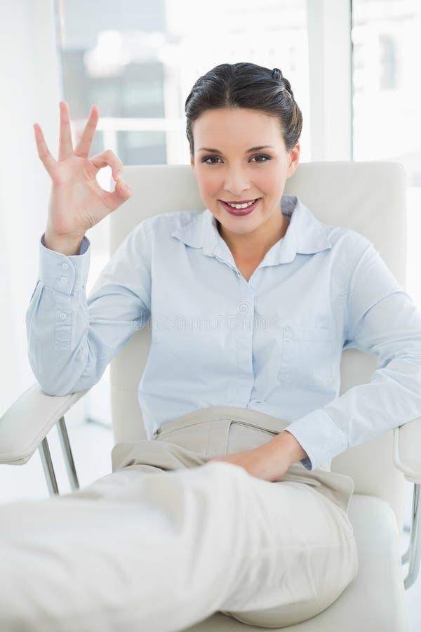 Donna di affari castana alla moda contenta che fa un gesto giusto immagini stock libere da diritti
